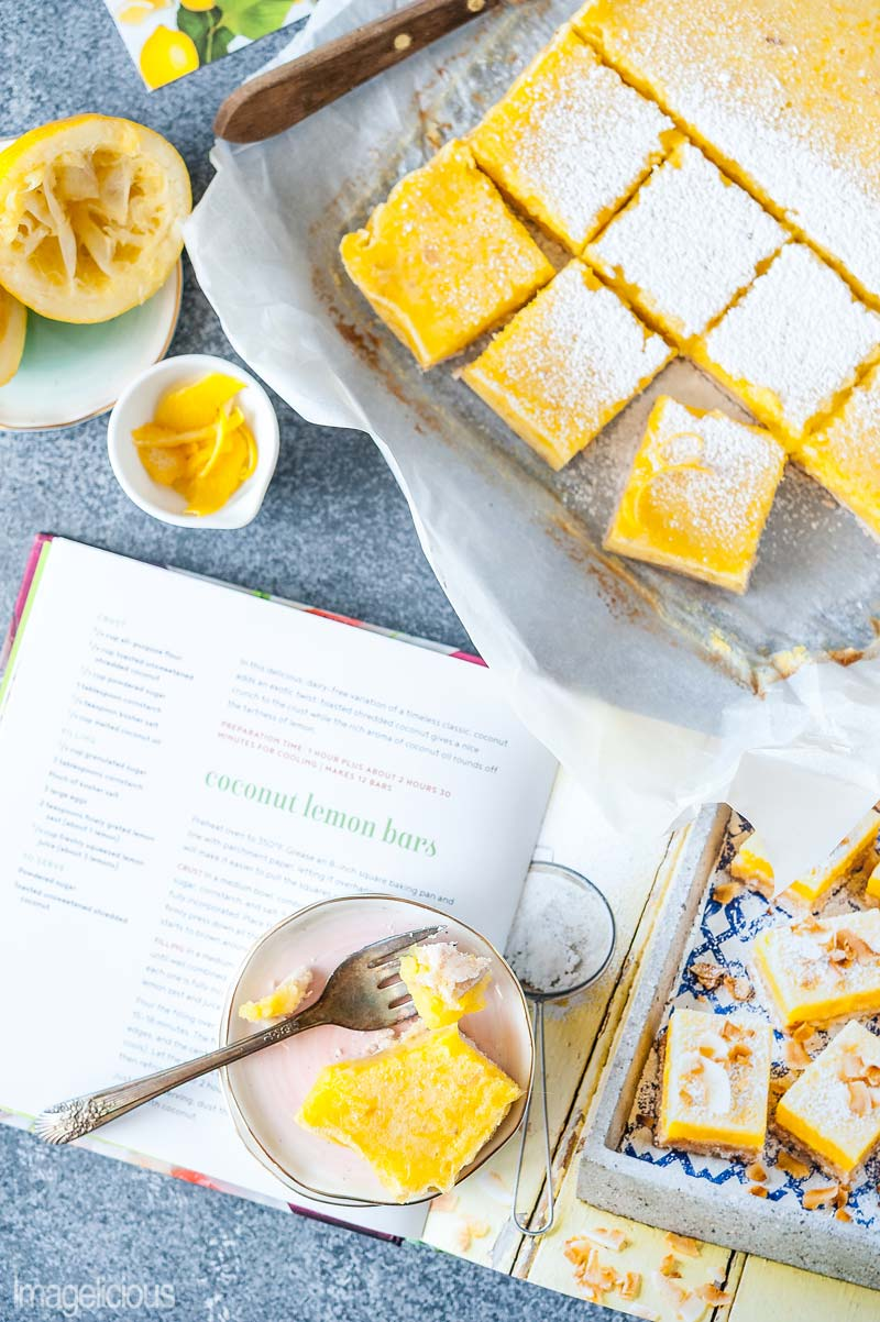 Top down view of Coconut Lemon Bars cut into suqares with a few lemons and lemon zest around it. Also an open cookbook and a plate with another Coconut Lemon Bar on top of the cookbook open to the recipe of that dessert
