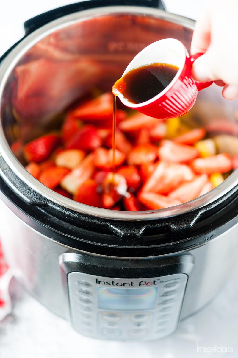 Instant Pot filled with strawberries and a hand pouring maple syrup into it