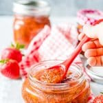 Closeup of a Strawberry Chia Jam with a hand holding a spoon inside a jar. Fresh strawberries in the background with a red napkin and another jar