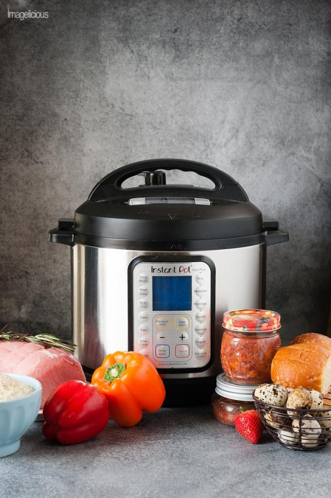 Instant Pot with a few foods around it: jam made in Instant Pot, eggs, bread, peppers, rice, pork