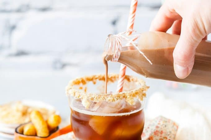 Glass filled with Peanut Butter Iced Coffee and homemade creamer being poured into it. There are peanut butter puffs scattered around the glass