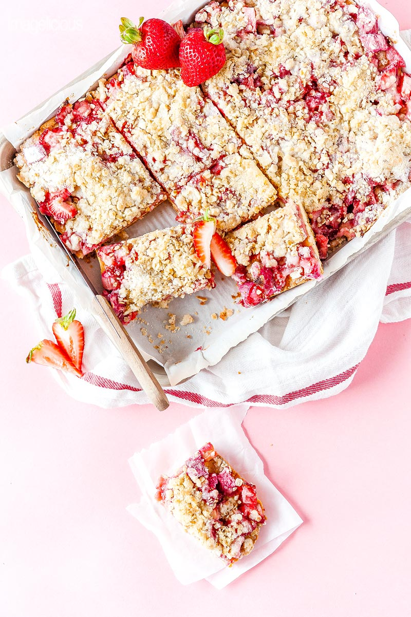 Top down view of a tray of Strawberry Rhubarb Bars and another bar next to it