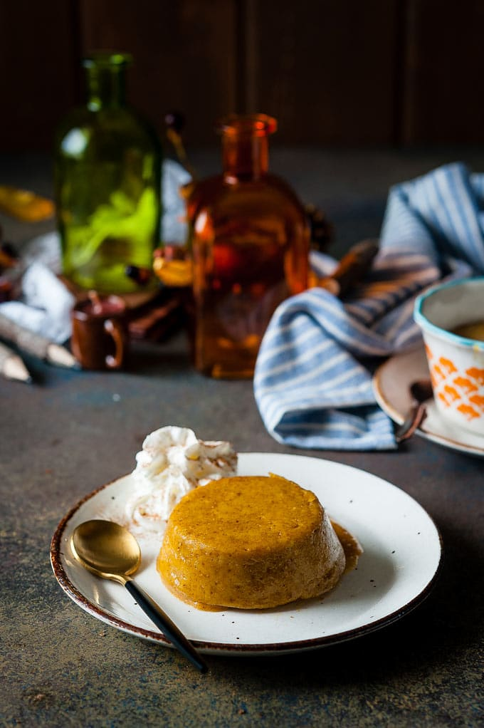 Instant Pot Pumpkin Pudding Cake on a plate with whipped cream on the side. A few fall-styled decorations in the background, blurred