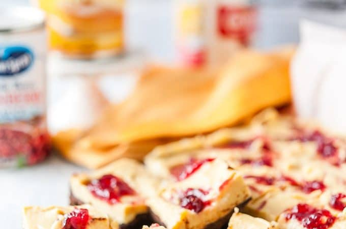 Photo of Pumpkin Cranberry Fudge cut up into serving pieces with a few cans in the background