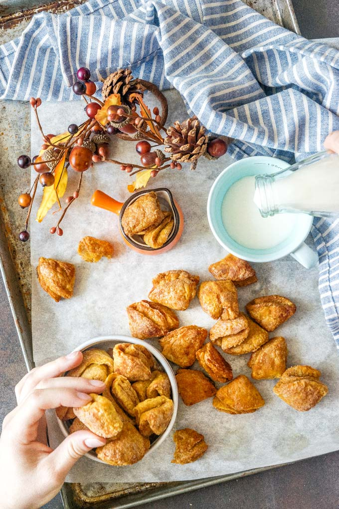 Pumpkin Ricotta Cookies on a sheet pan and in a bowl. A hand is picking up one cookie and milk is being poured into a cup