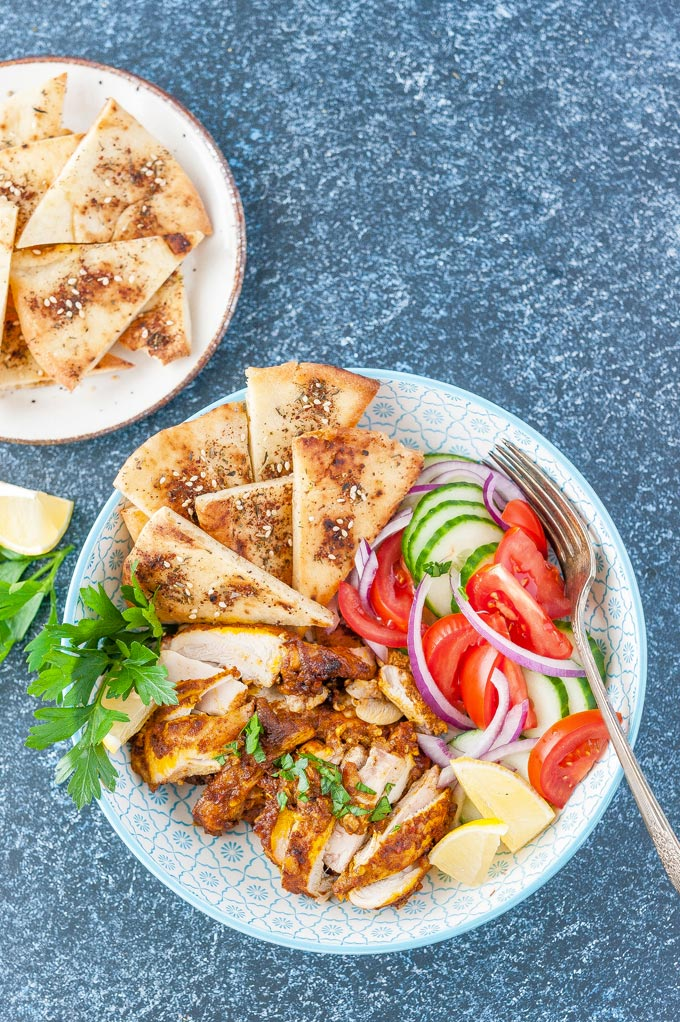 Top down view of a bowl of chicken shawarma with some fresh veggies and baked pitas. A plate of baked pitas is next to the bowl