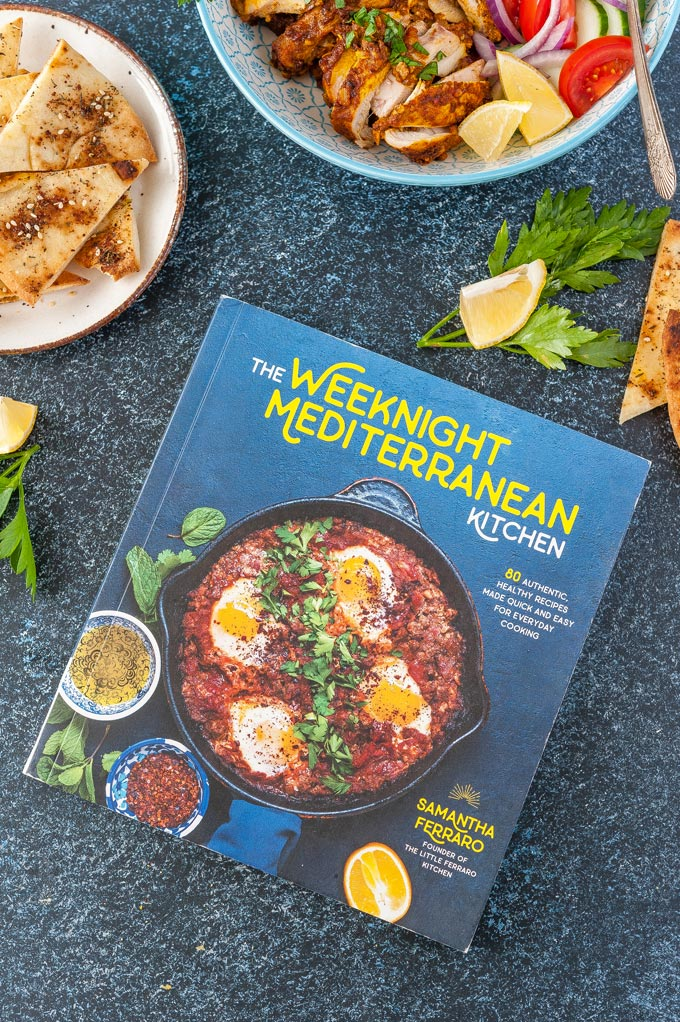Photo of a cookbook called The Weeknight Mediterranean Kitchen Cookbook with a few bowls of food made from this cookbook surrounding it
