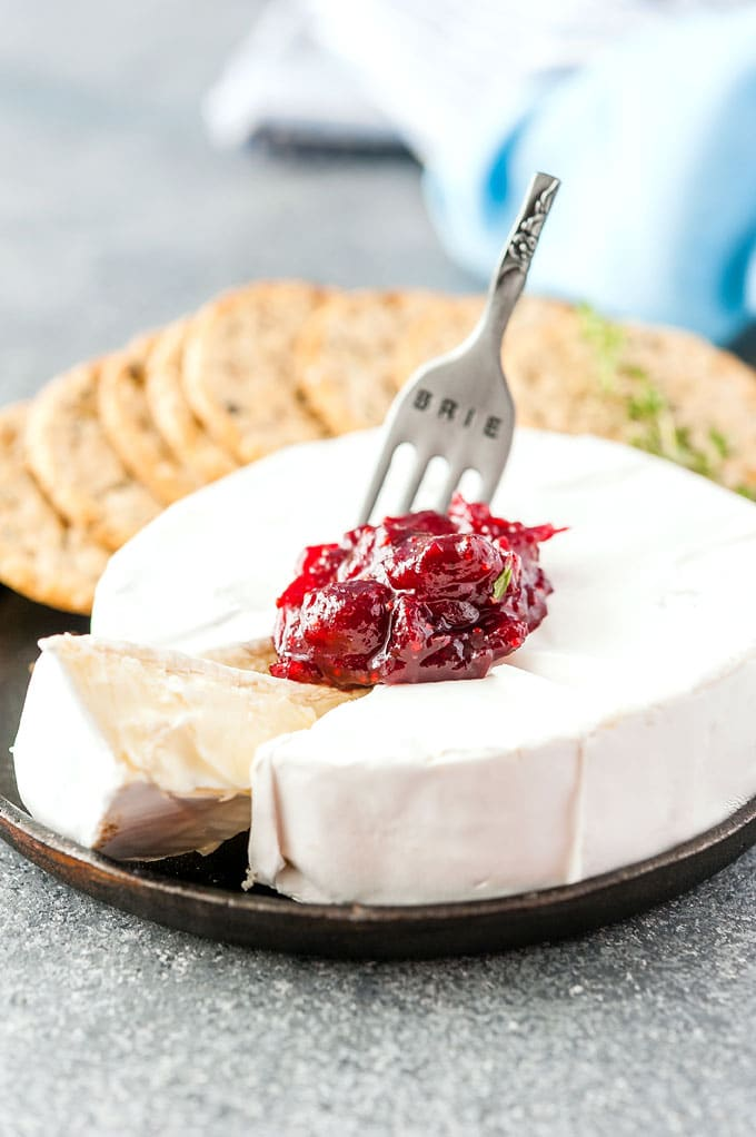 A wheel of Brie with a spoonful of Instant Pot Maple Cranberry Sauce on top of it