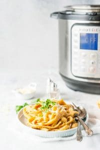 Photo of a plate of Instant Pot Pumpkin Fettuccine Alfredo with an Instant Pot in the background