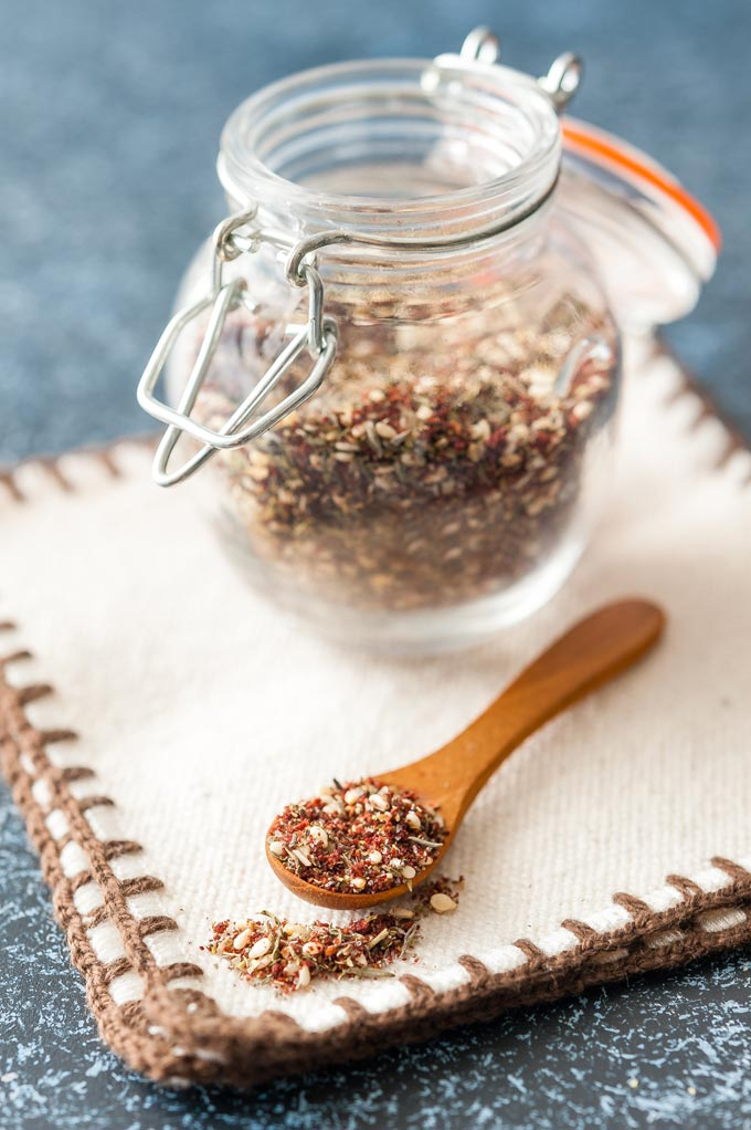 A small jar of Zaatar spice mix with a spoonful of the mix in front of it on a napkin