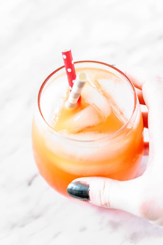 Hand holding a glass of Sparkling Campari Orange