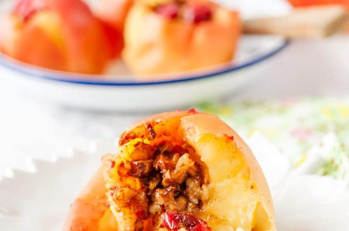 Closeup view of an Instant Pot Baked Apple cut open and the filling spilling out. More baked apples in the background