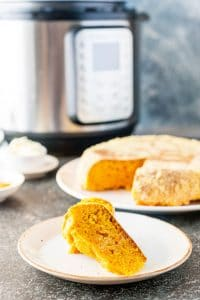 Slice of Instant Pot Cornbread with the rest of the cornbread in the background and an Instant Pot behind it