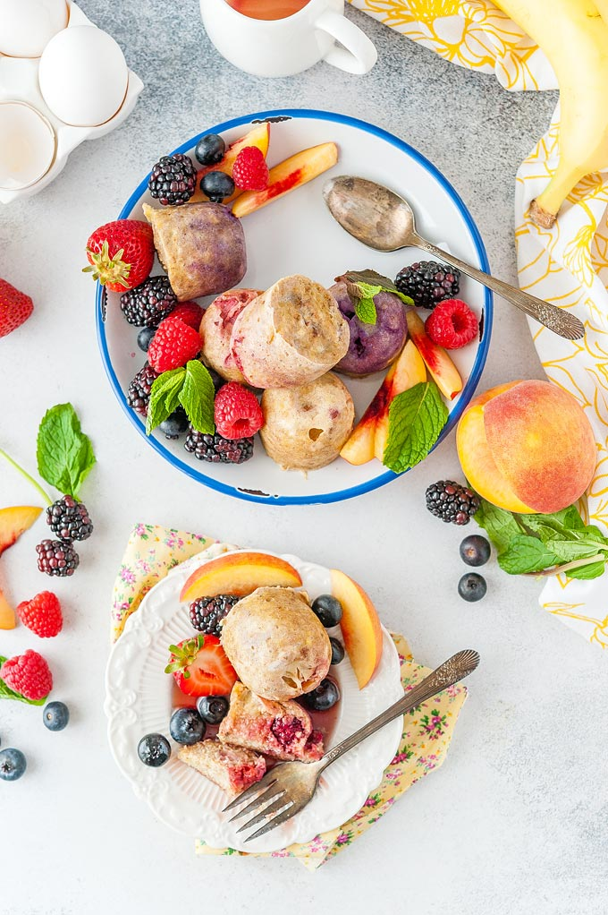 Top down photo of a plate with Fruity Egg Bites and a small plate with a few egg bites, cutup and covered in maple syrup. Lots of berries and fruits around on plates