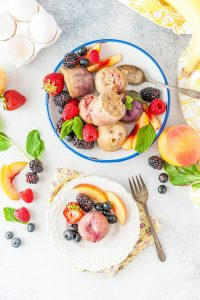 Top down photo of a plate full of Instant Pot Fruity Egg Bites and a small dessert plate with just one Instant Pot Fruity Egg Bite. Lots of fruits and berries around the egg bites
