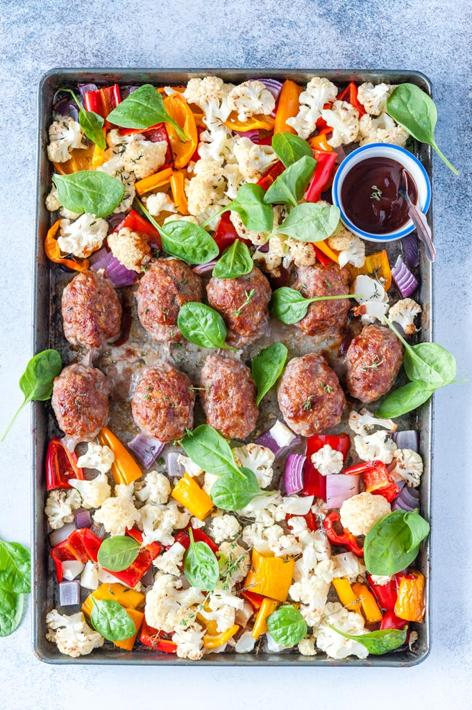 Sheet Pan Mini Meatloaves with Vegetables and spinach around them, also a small ramekin of extra bbq sauce
