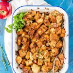 Baked Cornbread and Apple Stuffing in a pan with a spoon and a few whole apples on the side
