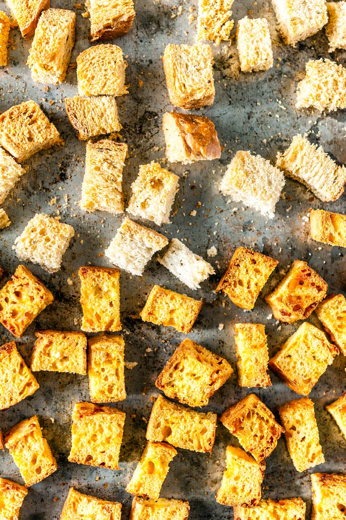 Top down view of a sheet pan with toasted bread and cornbread croutons