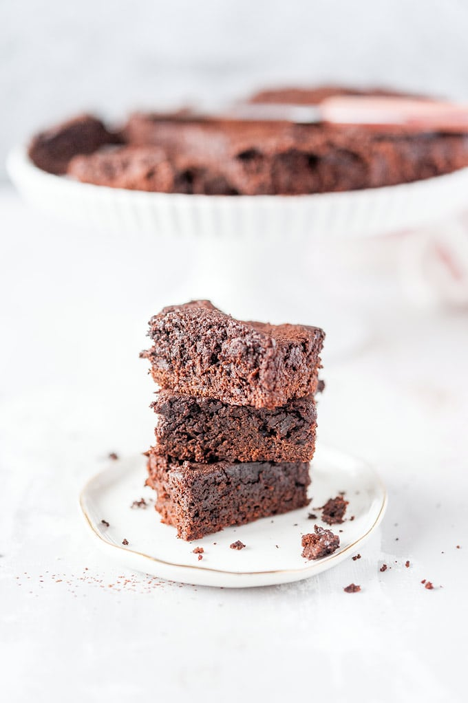 A stack of three Instant Pot Brownies on a small plate with crumbs around it and the rest of the brownies in the background