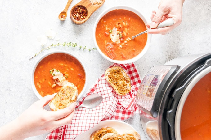 Top down view of two bowls of Instant Pot Tomato Orzo Soup with two people reaching into each bowl to take a spoonful