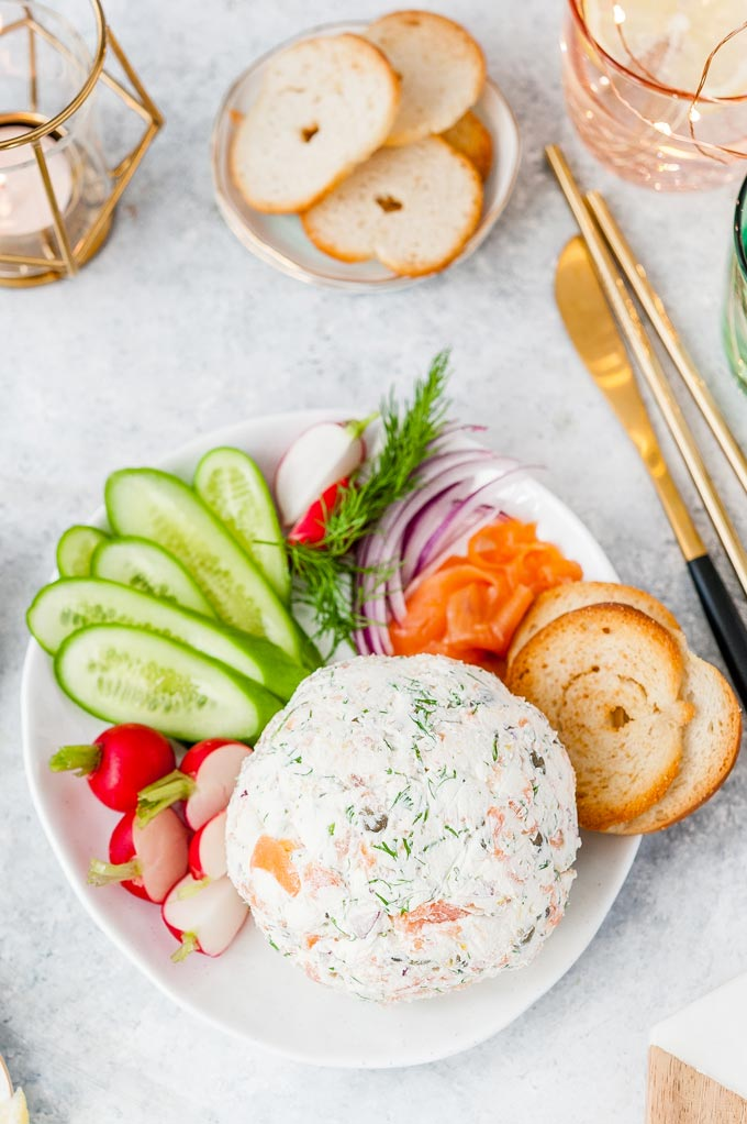 Top down view of a plate with Smoked Salmon Cheese Ball, radishes, cucumbers, crackers, more smoked salmon, and other fixings