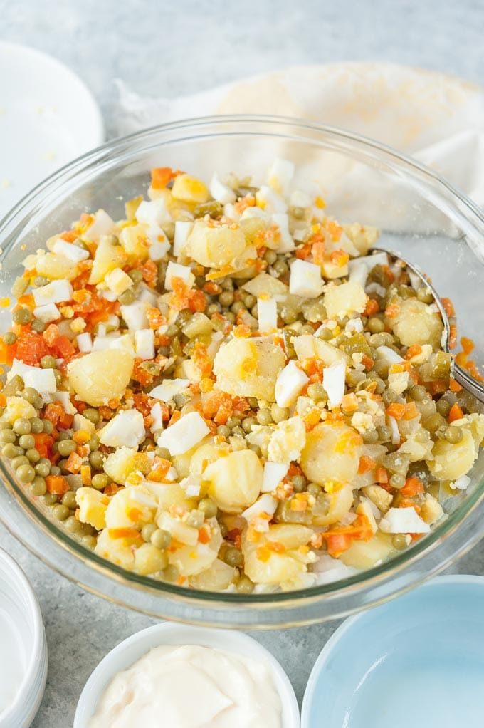 A bowl with all the ingredients for Russian Potato Salad mixed, except for the mayo