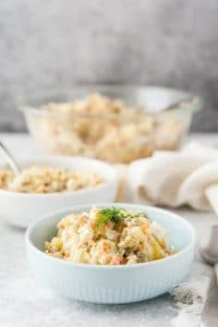 Two bowls of Russian Potato Salad with the rest of the salad in a big bowl in the background