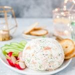 Whole round Smoked Salmon Cheese Ball on a plate with radishes, cucumbers, and crackers