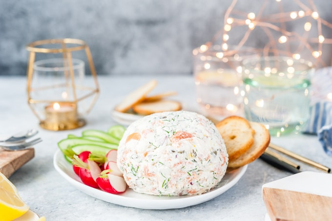 Horizontal photo of a Smoked Salmon Cheese Ball on a plate with vegetables and crackers