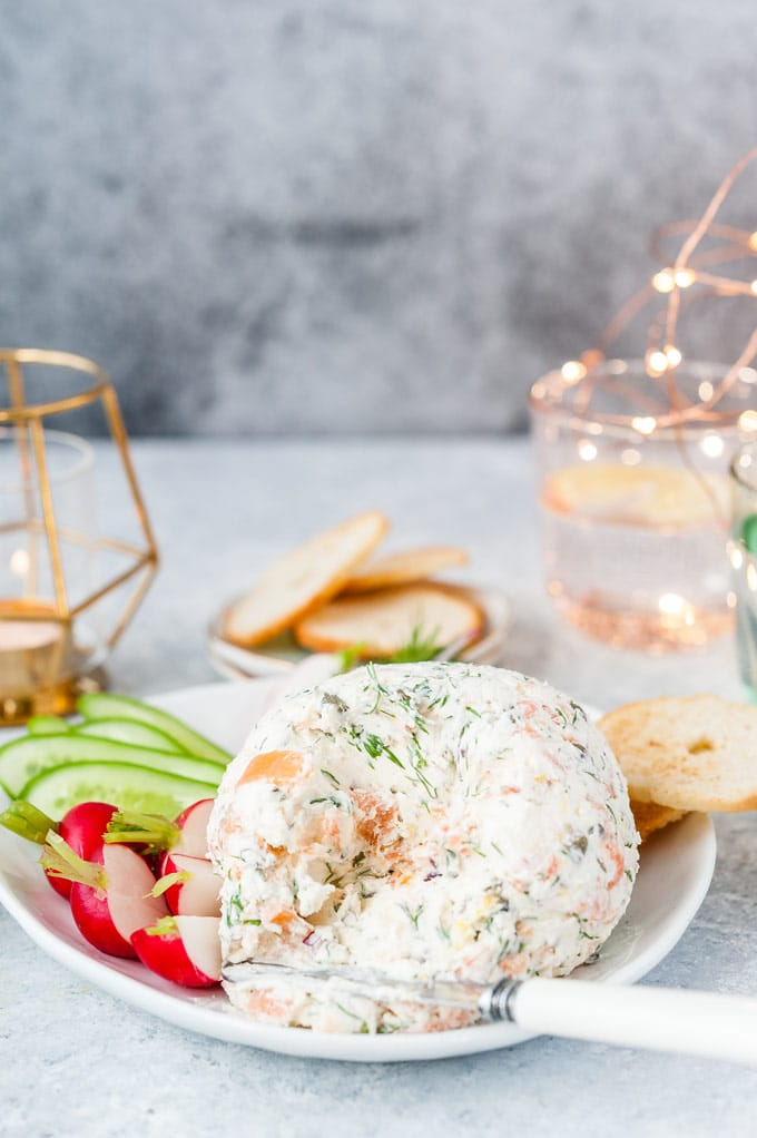 Half smoked salmon cheese ball with a knife and a few vegetables and crackers around it