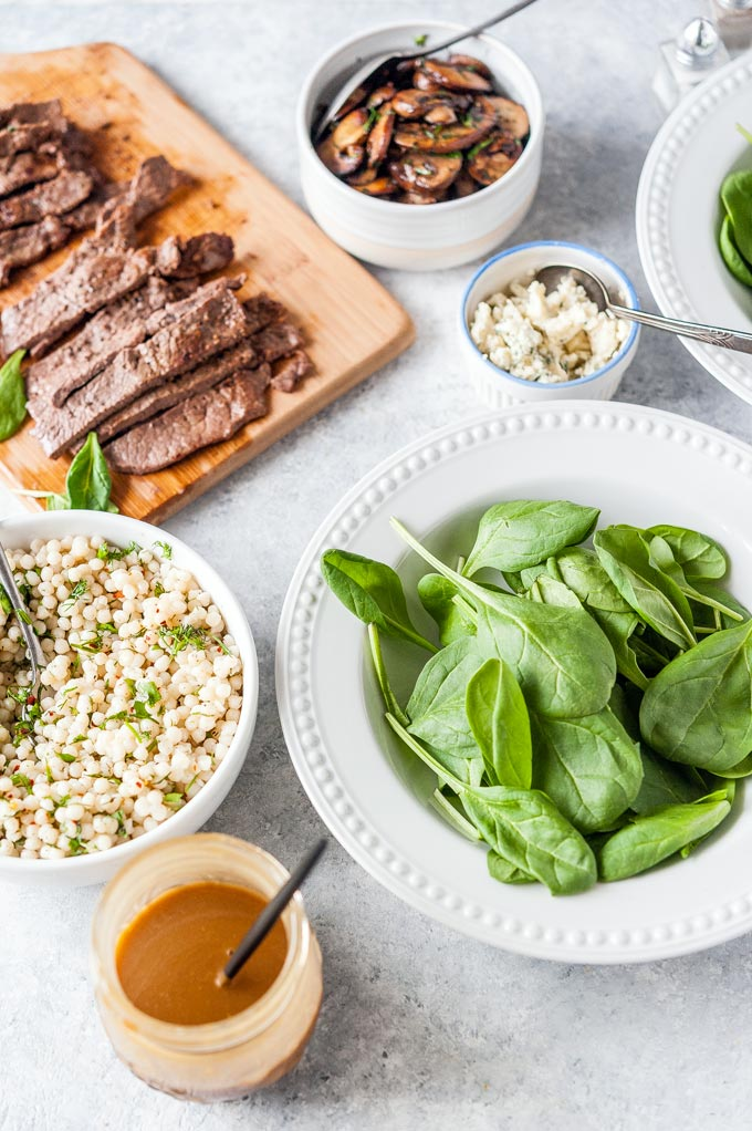 All the ingredients to make Steak and Mushroom Salad: sliced steak on a cutting bowl, cooked mushrooms, herbed couscous, mixed dressing, crumbled blue cheese, a bowl of spinach.