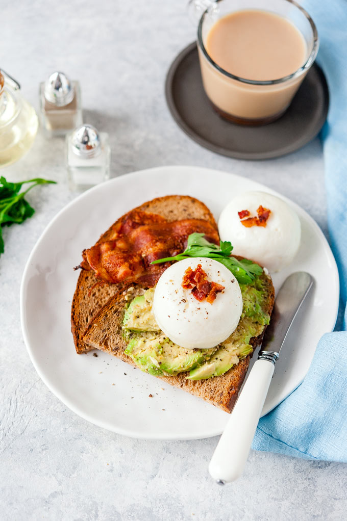 Top down view of a plate with rye toast with avocado, bacon and Instant Pot Poached eggs
