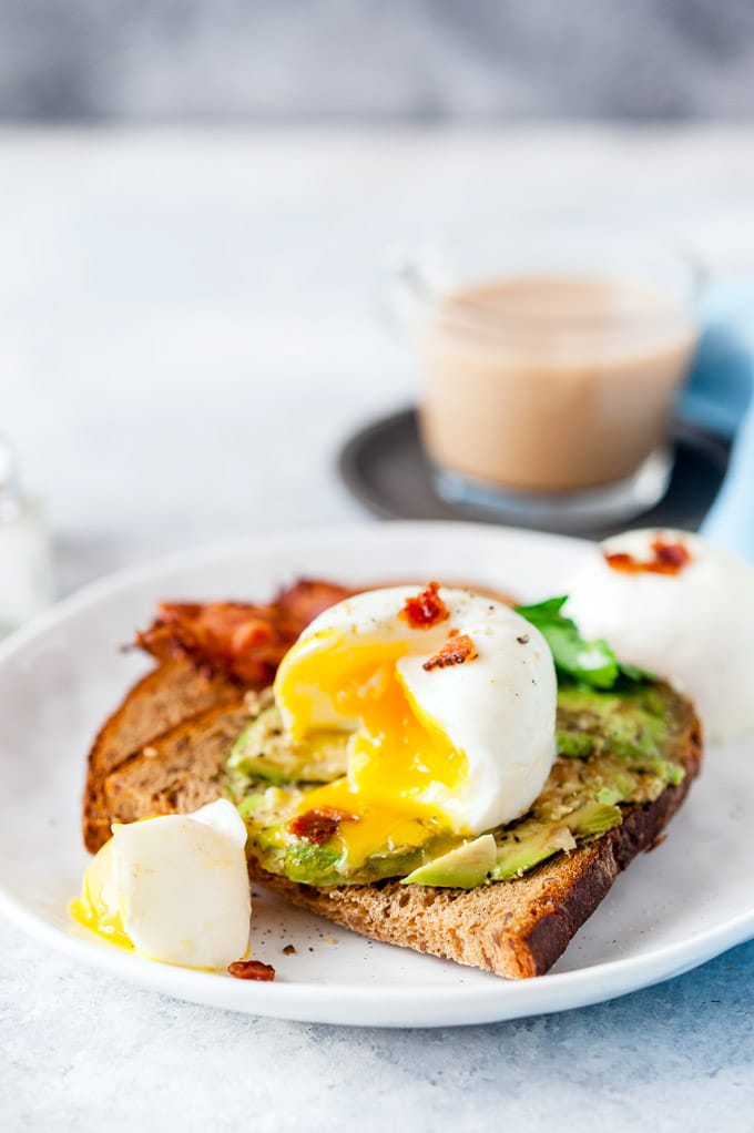 Instant Pot Poached Egg open with an egg yolk dripping over the avocado toast