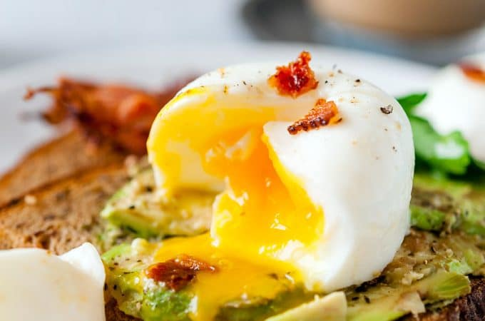 Closeup of an inside of poached egg with egg yolk dripping over avocado toast