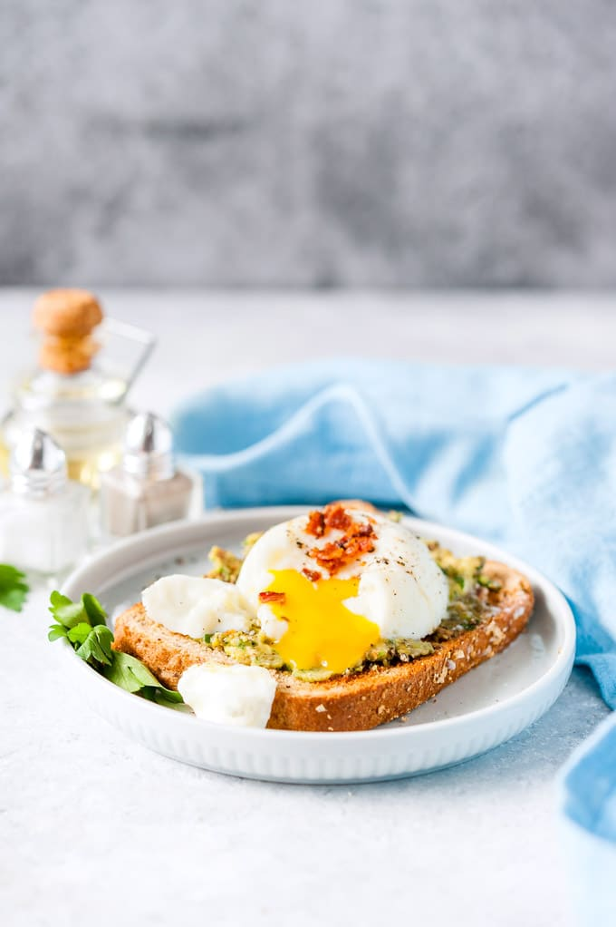 Instant Pot Poached Egg made in a glass bowl and on a toast with egg yolk dripping over it