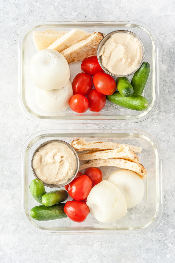 Hard boiled eggs in two meal prep containers with veggies, hummus, and pita