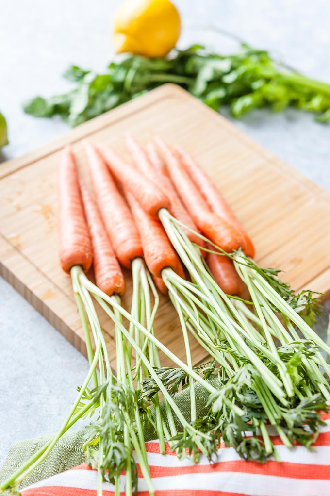Young bunch of carrots with tops attached on a cutting board
