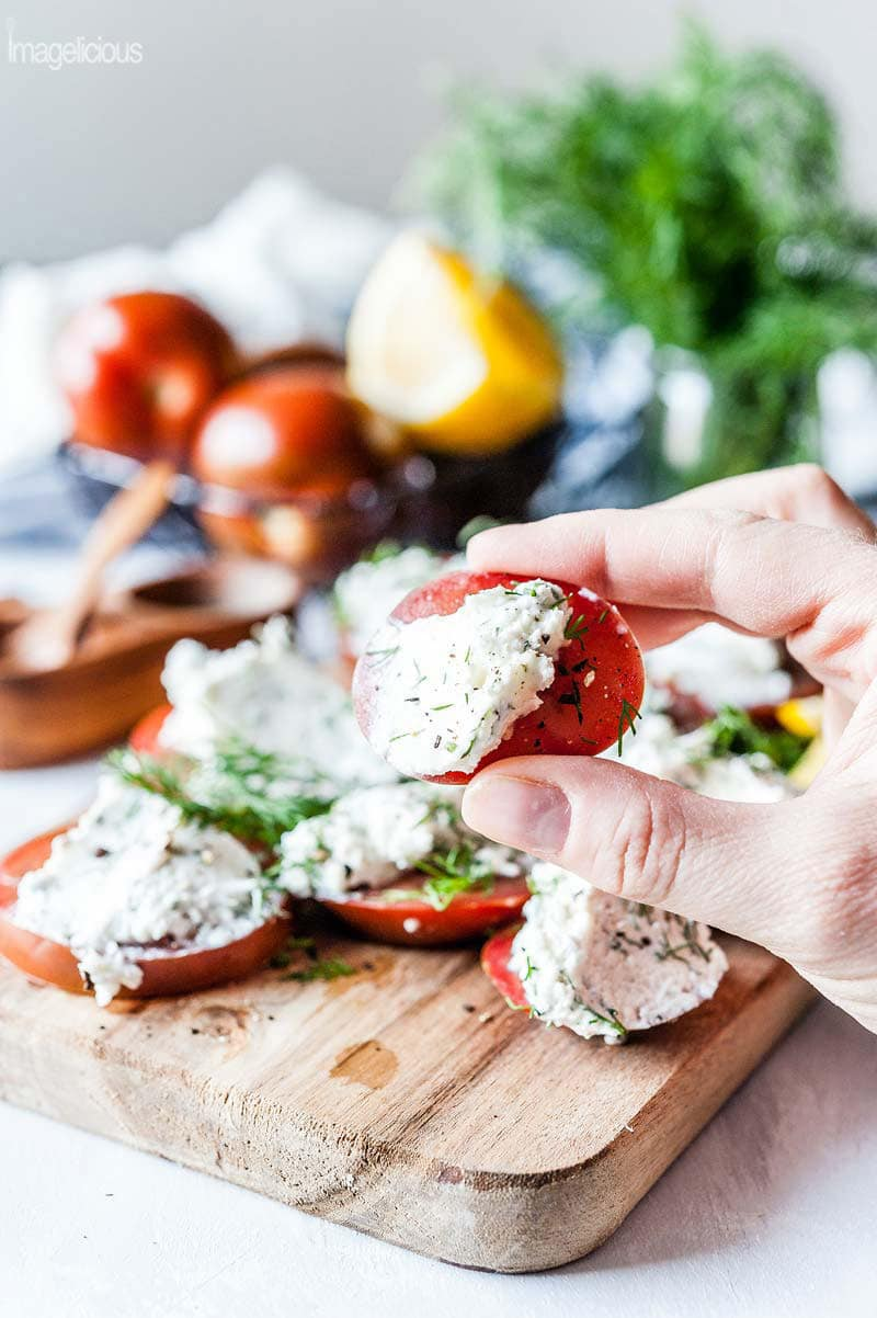 Hand holding a slice of tomato with goat cheese and dill spread. More tomatoes and herbs are in the background
