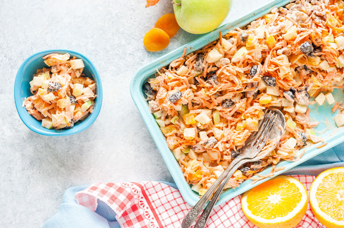 Bowl with Creamy Carrot Fruit Salad and the rest of the salad in a tray