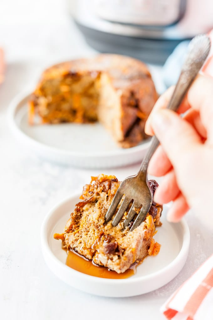 Hand sticking a fork into a slice of Instant Pot Carrot Cake Bread Pudding