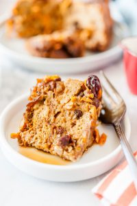 Close up of a slice of Carrot Cake Pudding covered in maple syrup