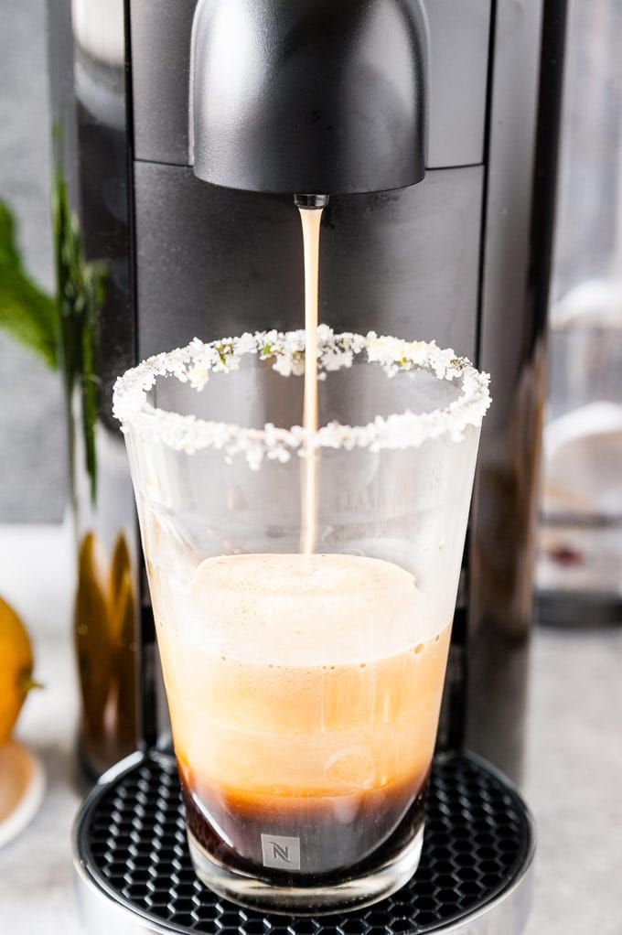 Glass with coffee pouring from Nespresso machine