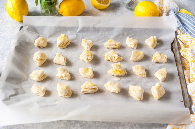 Sheet pan with a batch of unbaked lemon cream cheese cookies