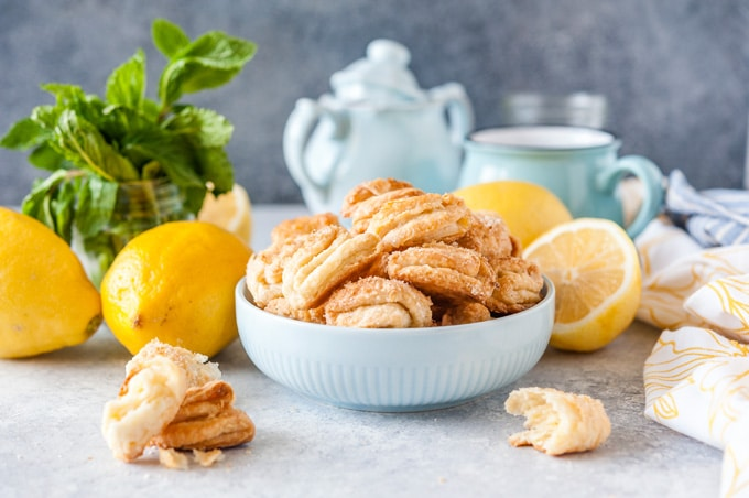 Bowl of Lemon Cream Cheese Cookies with lemons around it.