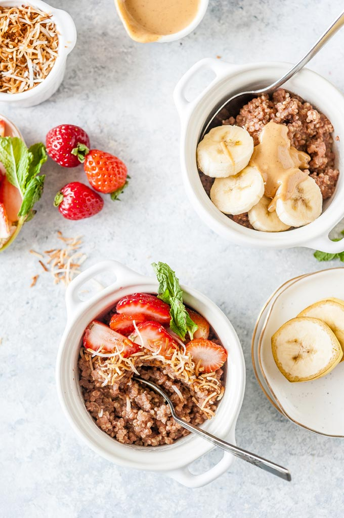 Two bowls of breakfast quinoa with various fruit toppings.