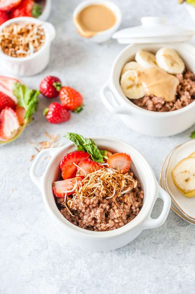 Two bowls with breakfast chocolate quinoa and various toppings.