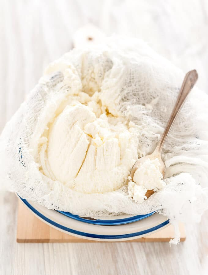Farmers cheese in a bowl with a spoon.