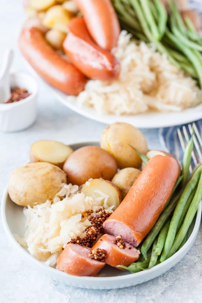 Closeup of cut cup sausage with mustard, sauerkraut, potatoes, and beans.