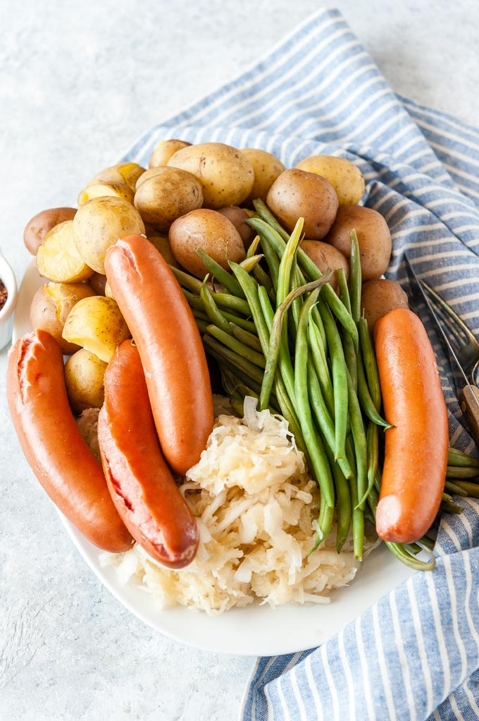 Platter with cooked potatoes, sausages, sauerkraut, and green beans.