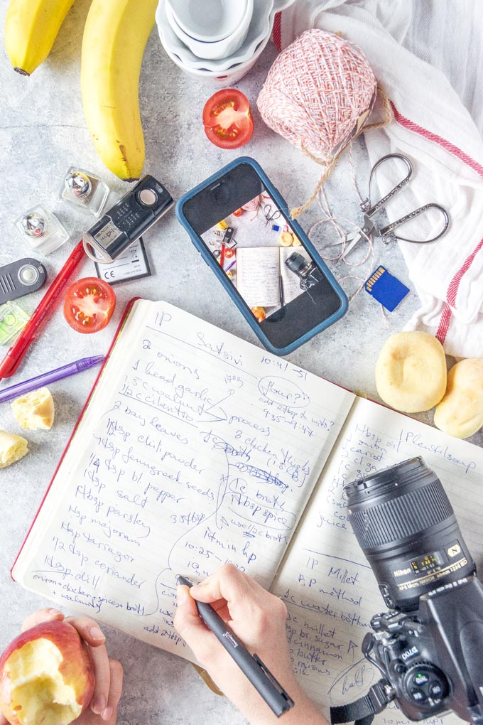 ingredients, camera, notebook, pens, cellphone and other props on a table.
